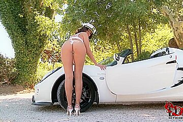Busty Linet poses outdoor by sports car